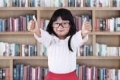 Beautiful schoolgirl in library — Stock Photo