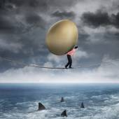 Businessman carrying golden egg above sea — Stock fotografie