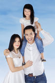 Family smiling at camera under blue sky — Stock Photo