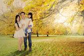 Full length of family under autumn tree — Stock Photo