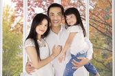 Joyful family under autumn tree — Foto Stock