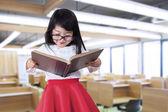 Little girl reads book in class — Foto Stock