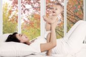 Playful mother with her baby on bedroom — Stockfoto