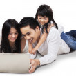 Family using laptop on the floor — Stock Photo #55333611