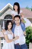Asian family in front of new house — Stock Photo