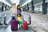 Family stand in airport hall — Stock Photo