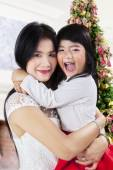 Mother hugs her daughter in christmas day — Stock Photo