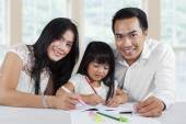 Cheerful parents help their child studying — Stock Photo