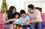 Happy family hold a story book — Stock Photo