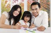 Happy parents help their child studying — Stock Photo