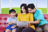 Little boy and his family using tablet — Stock Photo