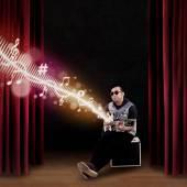 Male guitarist sitting on amplifier — Stockfoto
