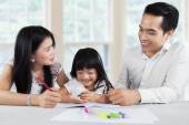 Preschool girl studying with parents — Stock Photo