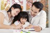 Two parents assist their child studying — Stock Photo