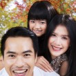 Attractive family smiling under autumn tree — Stock Photo #56479143