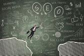 Businesswoman leaps through gap on the blackboard 4 — Stock Photo