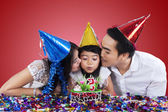 Family celebrate birthday with red background — Foto de Stock