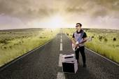 Guitarist playing guitar on the road — Stockfoto