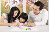 Young parents help their child studying — Stock Photo
