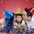 Two parents kiss their child in birthday party — Stock Photo #56490123