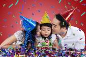 Two parents kiss their child in birthday party — Stock Photo