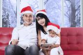 Family with christmas hat on couch — Foto de Stock