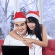 Woman hug her boyfriend while using laptop — Stock Photo #57041093