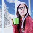 Girl in winter clothes drinking hot beverage — Stock Photo #57170767