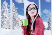 Girl in winter clothes drinking hot beverage — Stock Photo