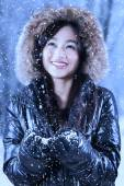 Happy woman with fur jacket under snowfall — Stock Photo