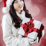 Girl wearing santa hat holding gift box — Stock Photo #58037527