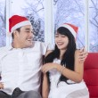 Happy couple in christmas hat laughing — Stock Photo #58037743