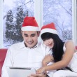 Young couple in santa hat using tablet — Stock Photo #58039931