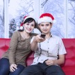 Couple wearing christmas hat watching tv — Zdjęcie stockowe #58168147