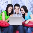 Group of friends using laptop on sofa — Stock Photo #58168647