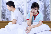 Couple sitting separately on bed — Stock Photo