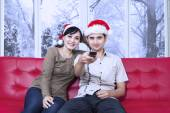 Couple wearing christmas hat watching tv — Stockfoto