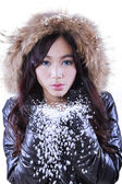 Girl with fur jacket blowing snow — Stock Photo