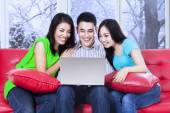 Group of friends using laptop on sofa — Foto Stock