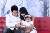 Parents using tablet with their daughter — Stock Photo