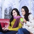 Two girl in winter clothes using laptop — Stock Photo #58170395