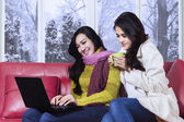Two ladies using laptop in winter day — Stock Photo