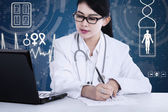 Female doctor working at the desk — Stock Photo