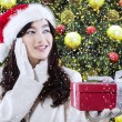 Girl with a gift near christmas tree — Stock Photo #59246985
