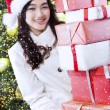 Girl with gifts near christmas tree — Stock Photo #59247011