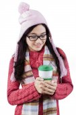 Female holding hot drink in studio — Stock Photo