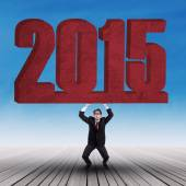 Strong businessman lifting number 2015 — Stock Photo