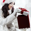 Shocked girl in winter clothes opening a gift — Stock Photo #59923923