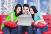 Three asian teenagers with laptop at home — Stock Photo