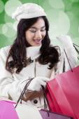 Attractive woman looking gift bags — Stock Photo